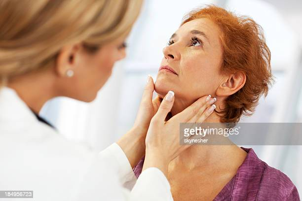 female doctor examining her patient. - goiter stock pictures, royalty-free photos & images
