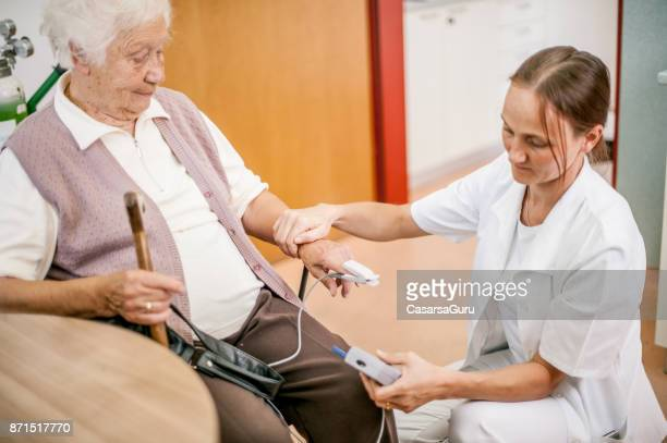Female Doctor Examining Senior Woman Pulse With  Pulse Oxymeter