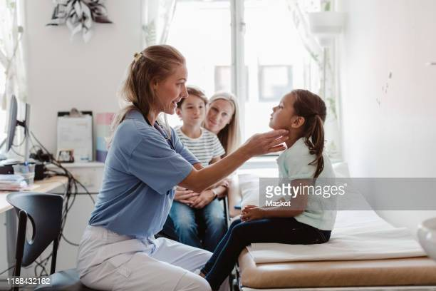 female doctor examining throat of girl while family sitting in medical room - patients brothers stock pictures, royalty-free photos & images