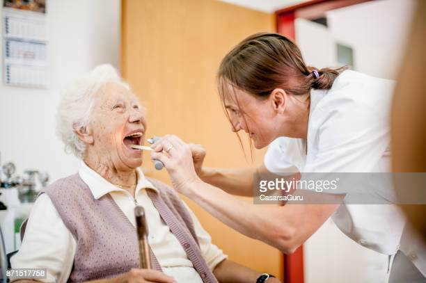 female doctor examining throat of senior woman in rest home - throat photos stock photos and pictures