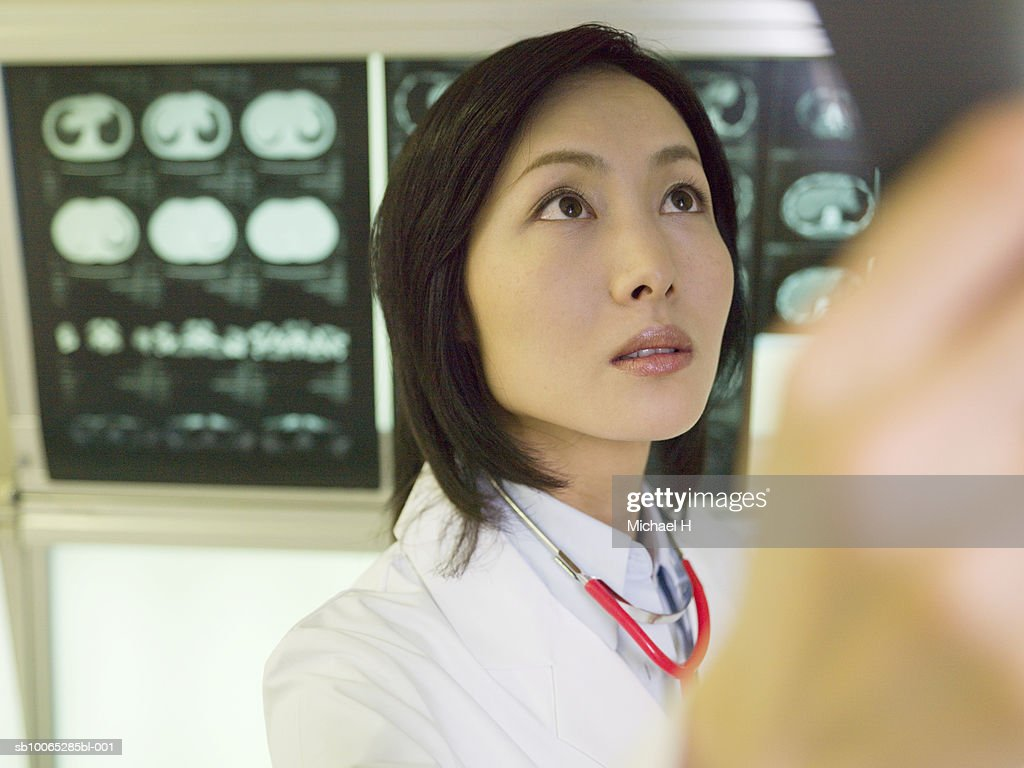 Female doctor examining X-ray picture in hospital : Foto stock