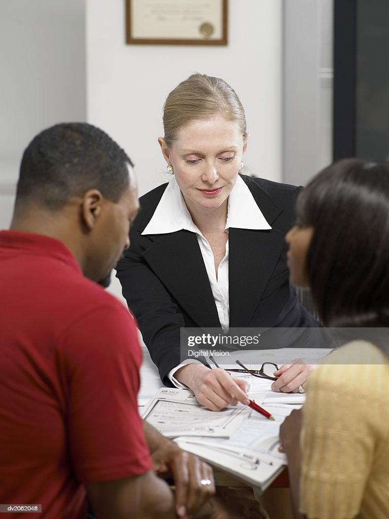 Female Doctor Explaining a Document to a Couple in Her Clinic : Stock Photo