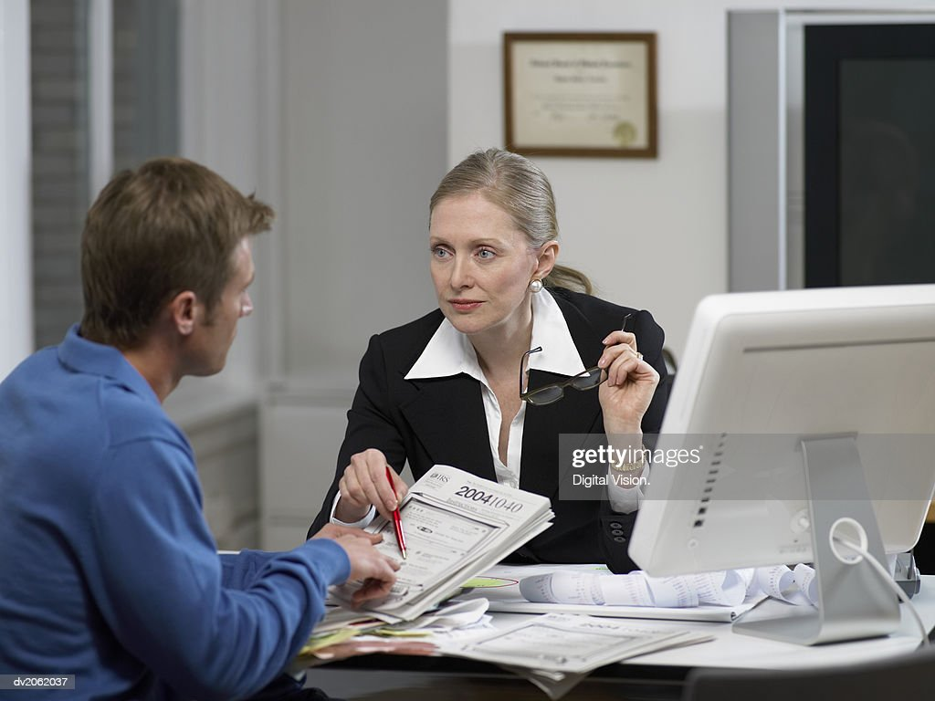 Female Doctor Explaining a Document to Her Male Patient at Her Clinic : Stock Photo