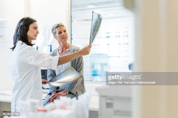 female doctor explaining x-rays to mature patient - x ray image stock pictures, royalty-free photos & images