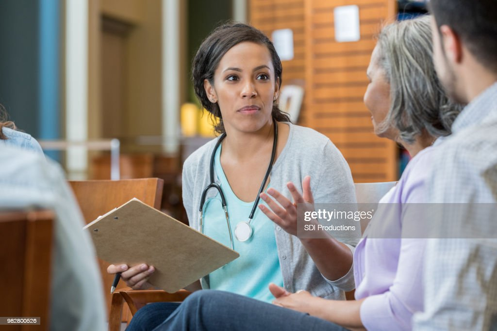 Female doctor explains something to patients : Stock Photo