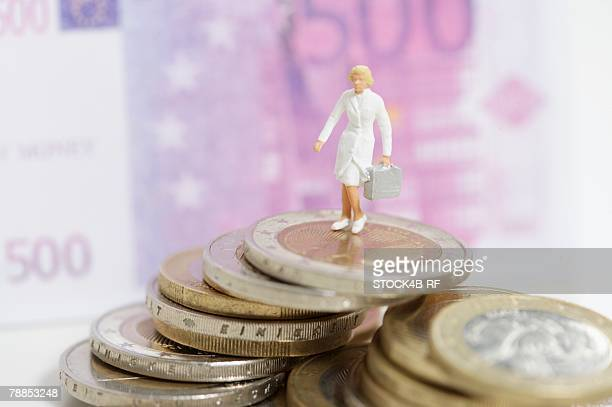 Female doctor figurine on a stack of coins