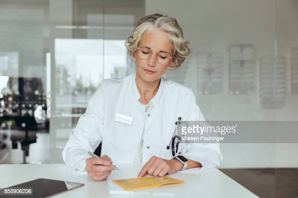 Female doctor filling out certificate of vaccination