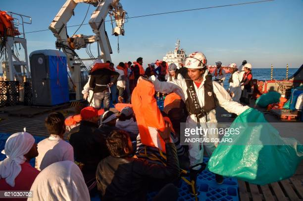 TOPSHOT A female doctor gives life jackets to migrants and refugees before their transfer from the Topaz Responder ship run by Maltese NGO Moas and...