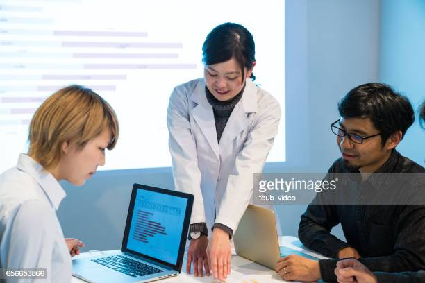 Female doctor giving a presentation in a meeting room with projection equipment