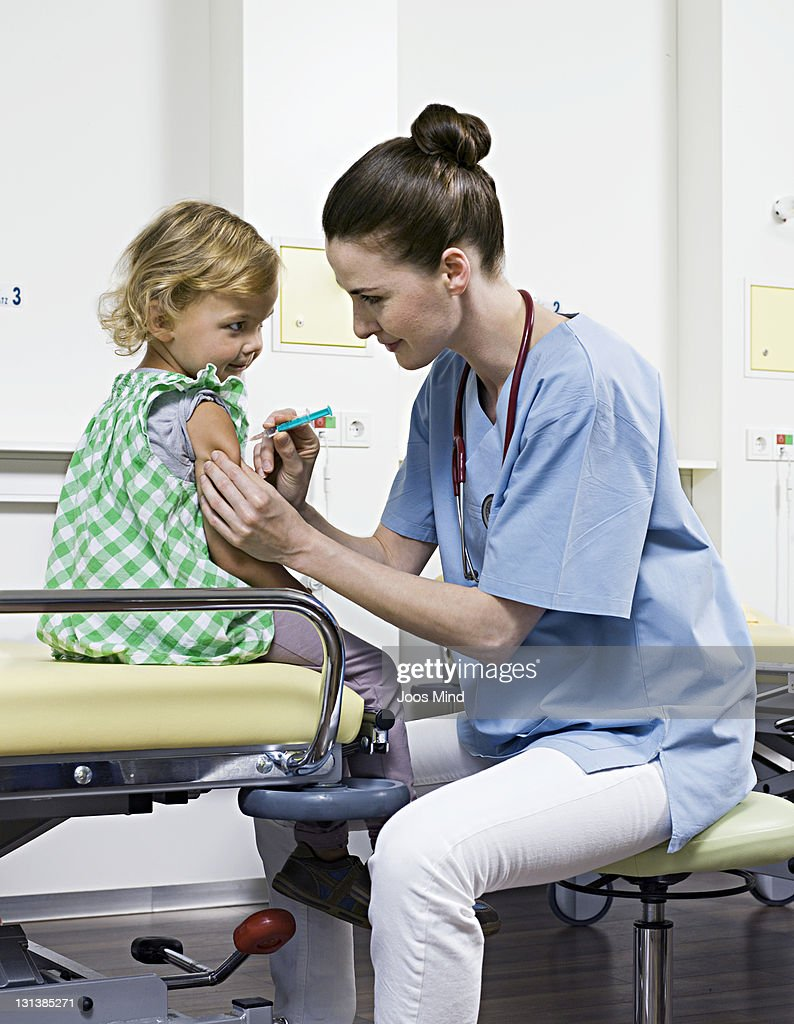 female doctor giving child injection : Foto de stock