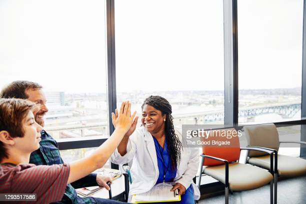 female doctor giving high five to boy in hospital waiting room - healthcare stock pictures, royalty-free photos & images