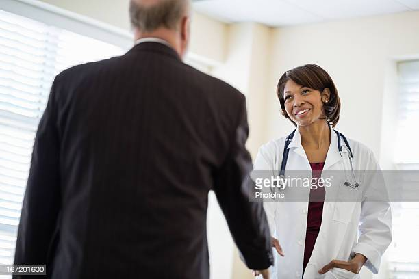 Female Doctor Greeting Businessman In Clinic