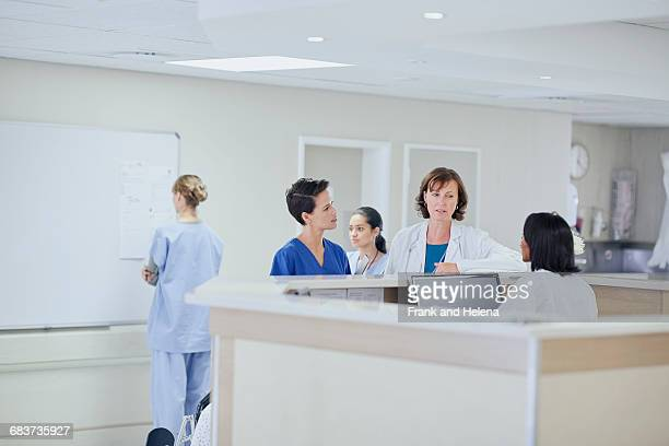 Female doctor having discussion with nurses at nurses station in hospital
