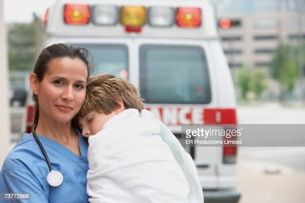 female doctor holding boy wrapped in blanket - hero and not superhero stock pictures, royalty-free photos & images