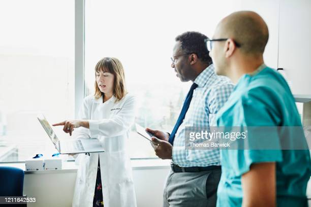 female doctor holding laptop discussing patient information with medical team in exam room - healthcare stock pictures, royalty-free photos & images