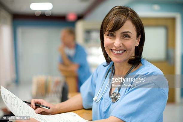female doctor holding medical records, smiling, portrait - infermiera foto e immagini stock