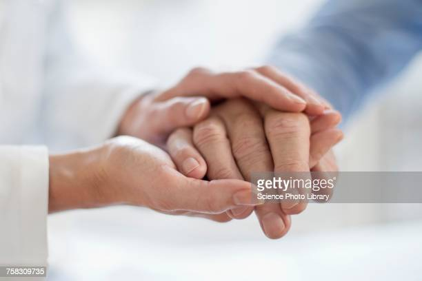 Female doctor holding patients hand