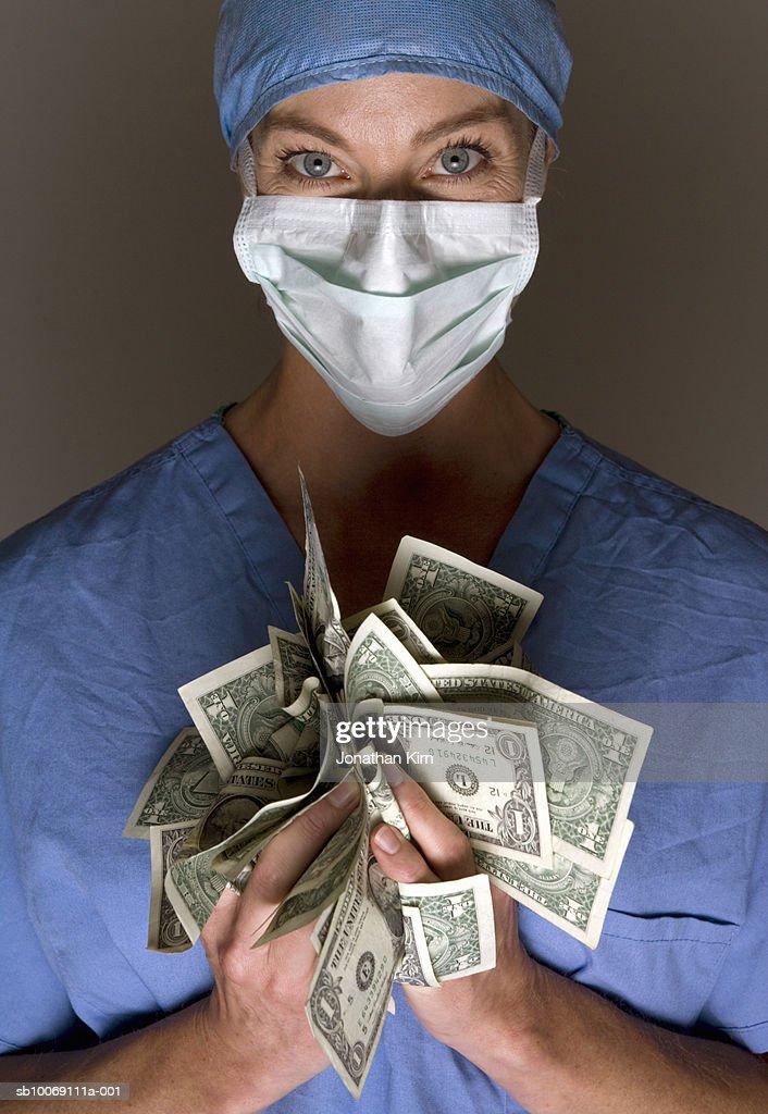 Female doctor holding US dollars, portrait : Stockfoto