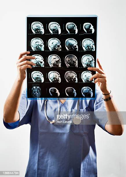 Female doctor holds up mri in front of her face