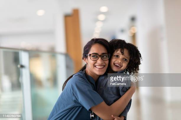 female doctor hugging her toddler patient - body care stock pictures, royalty-free photos & images