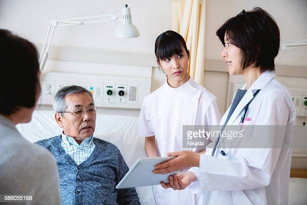 female doctor in a hospital explaining diagnosis on a tablet - outpatient care stockfoto's en -beelden