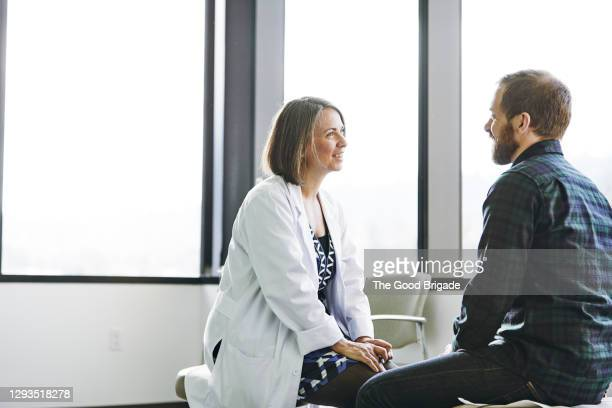 female doctor in discussion with male patient in exam room - doctor stock pictures, royalty-free photos & images