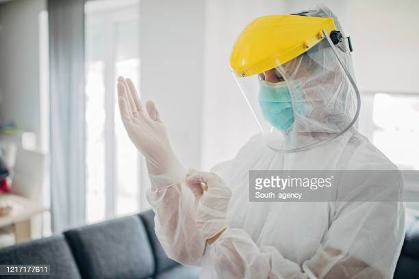 female doctor in full protective suit in home inspection - protective workwear stock pictures, royalty-free photos & images