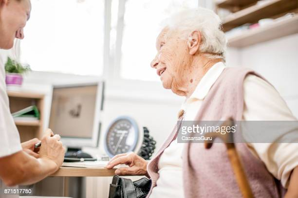 Female Doctor In Her Office Explaining Diagnosis To Senior Woman