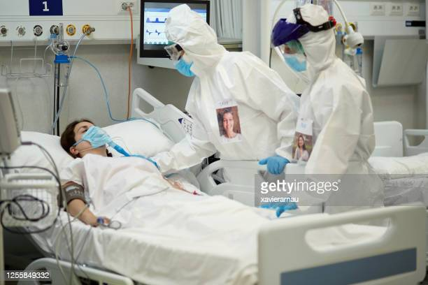female doctor in protective suit checking covid-19 patient - ventilator stock pictures, royalty-free photos & images
