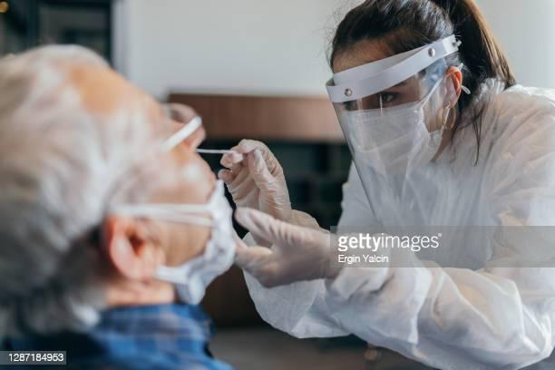ärztin im schutzanzug nimmt nasenabstrich-test von senior - wissenschaftliches experiment stock-fotos und bilder