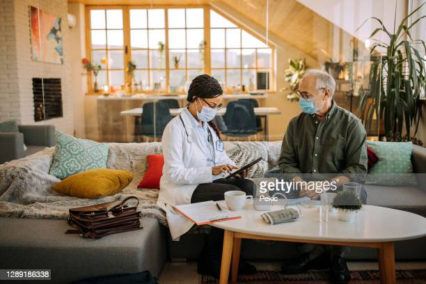 female doctor is at an in-home visit of her older patient - house call stock pictures, royalty-free photos & images