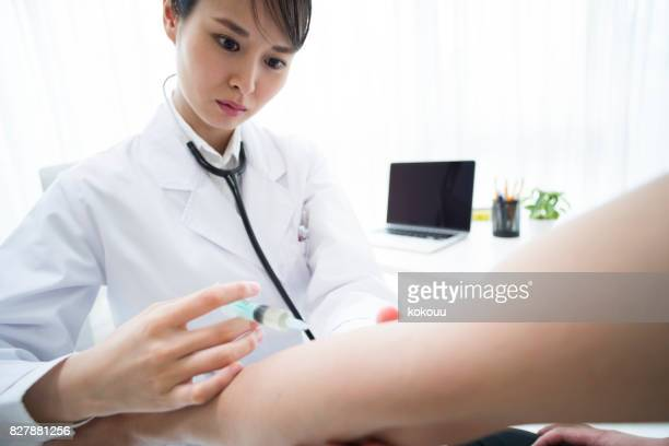 A female doctor is injecting the patient's arm.