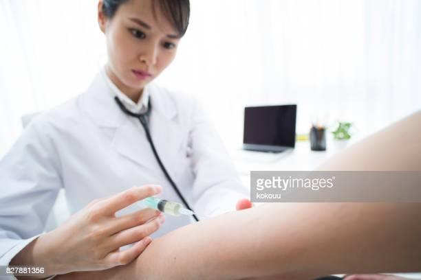 Eine Ärztin ist den Arm des Patienten injiziert.