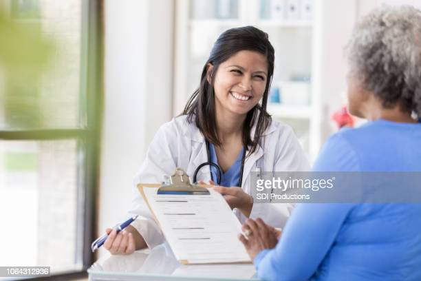 female doctor laughs with patient during paperwork - form filling stock pictures, royalty-free photos & images