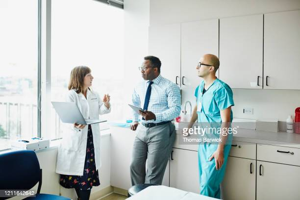 female doctor leading medical team discussion in hospital exam room - 医療とヘルスケア ストックフォトと画像