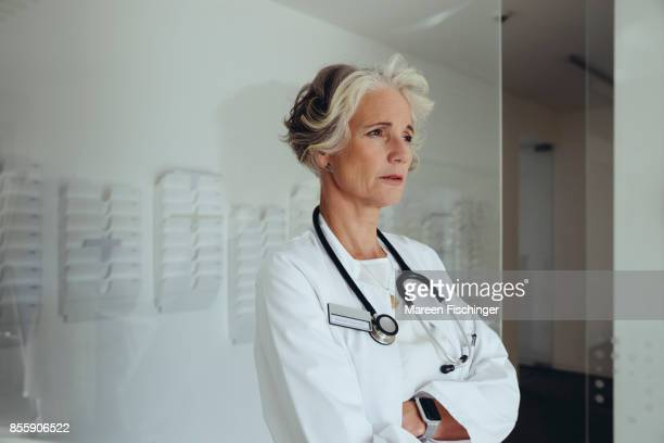 Female doctor leaning at glass wall, looking at somebody