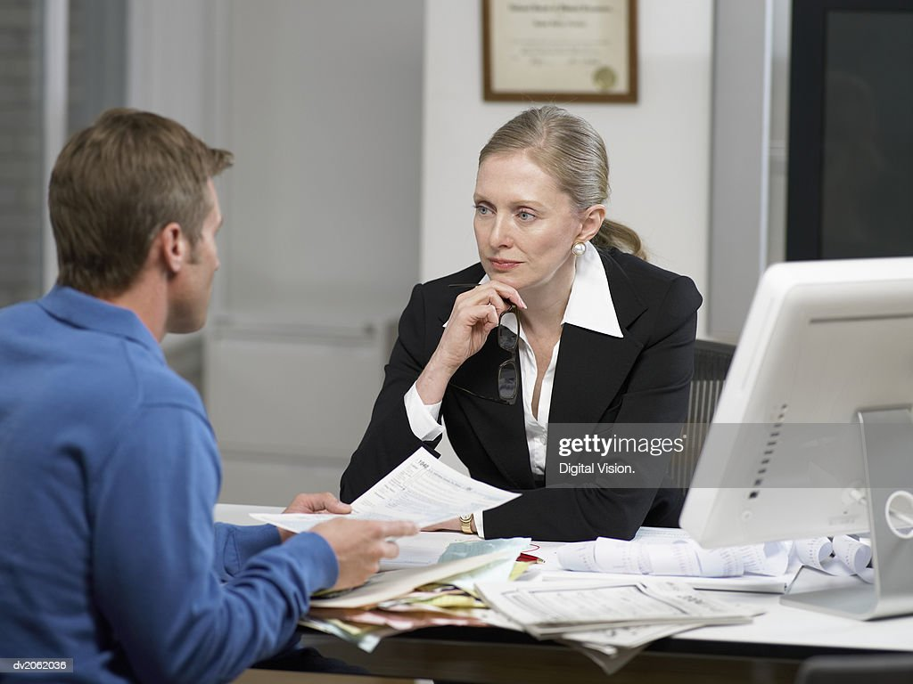 Female Doctor Listening to a Male Patient's Explanations : Stock Photo