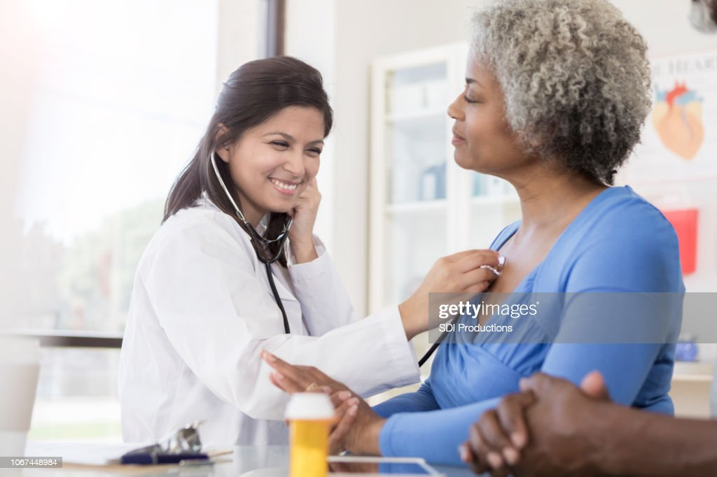 Female doctor listens to senior woman's lungs : Stock Photo
