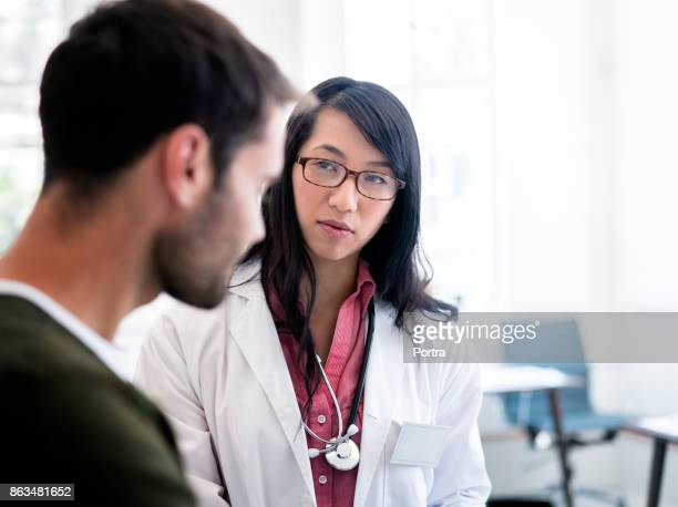 female doctor looking at male patient in clinic - visita imagens e fotografias de stock