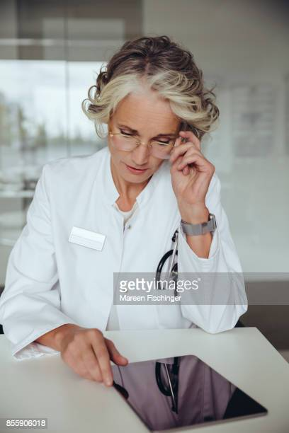 Female doctor looking at mobile tablet with worried look on her face