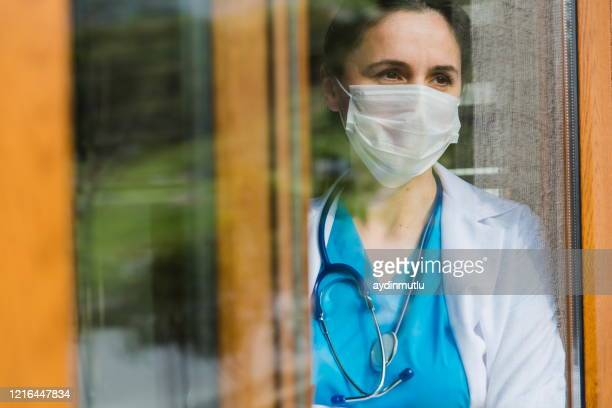médica do sexo feminino olhando pela janela do hospital - infectious disease - fotografias e filmes do acervo