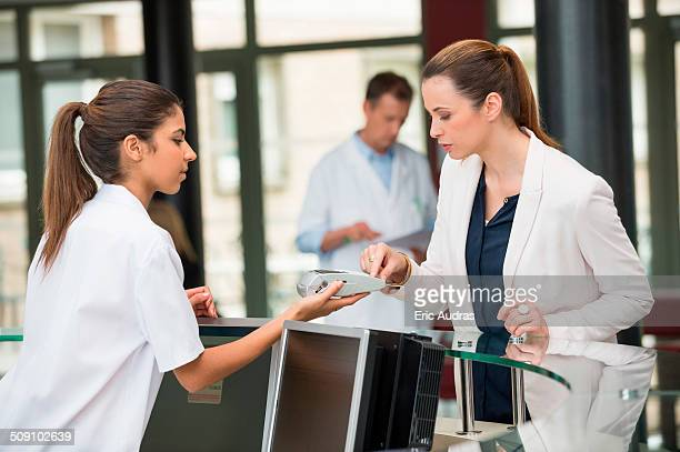 female doctor making payment with credit card at hospital reception desk - medical receptionist uniforms stock photos and pictures