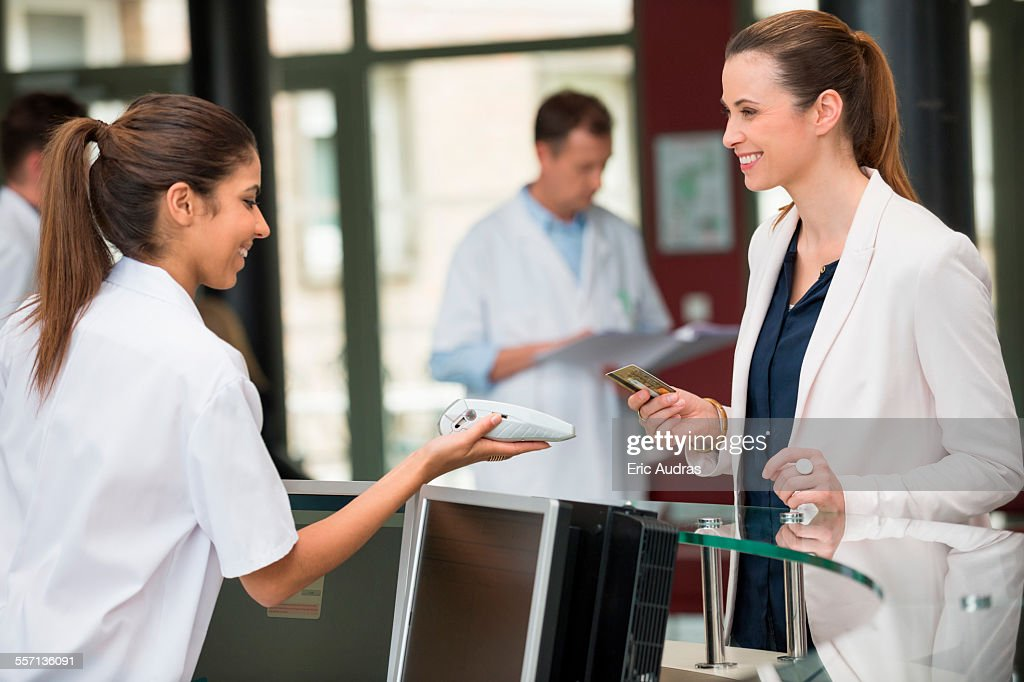 Female doctor making payment with credit card at hospital reception desk : Stock Photo