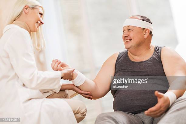 Female doctor measuring pulse of fat man after training.