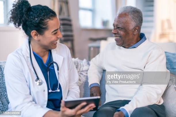 female doctor meeting with senior patient in his home - patient stock pictures, royalty-free photos & images