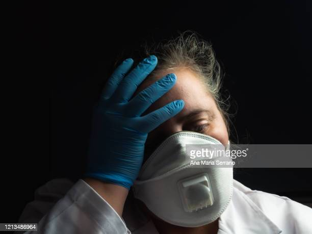a female doctor or scientist wearing a mask and lab coat with her hands on her head wearing protective gloves - pandemia fotografías e imágenes de stock