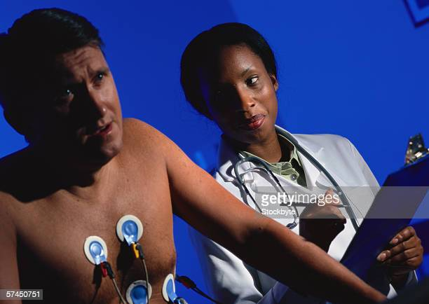 a female doctor performing a stress test on a man - stress test stock pictures, royalty-free photos & images