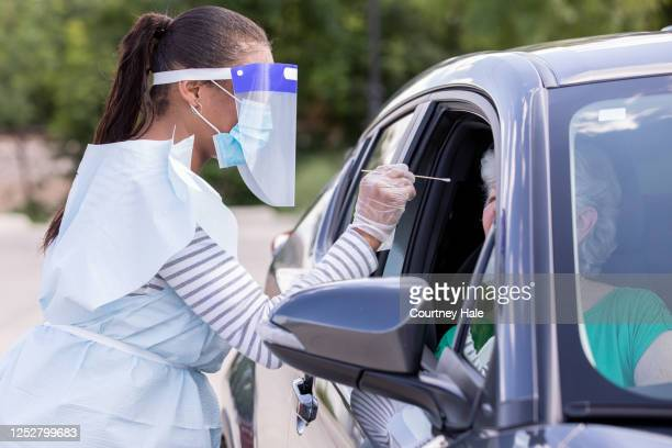 female doctor performing covid-19 tests while patients sit in cars - blood stock pictures, royalty-free photos & images