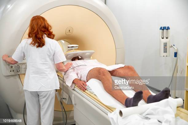 female doctor preparing young male patient for magnetic resonance head scan - epilepsy stock pictures, royalty-free photos & images