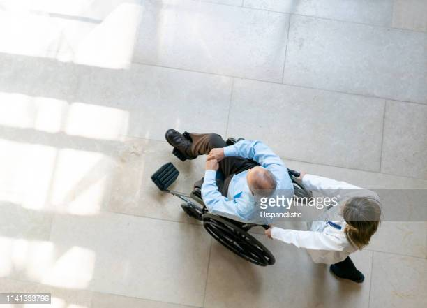 female doctor pushing male patient on wheelchair at the hospital - amputee stock pictures, royalty-free photos & images